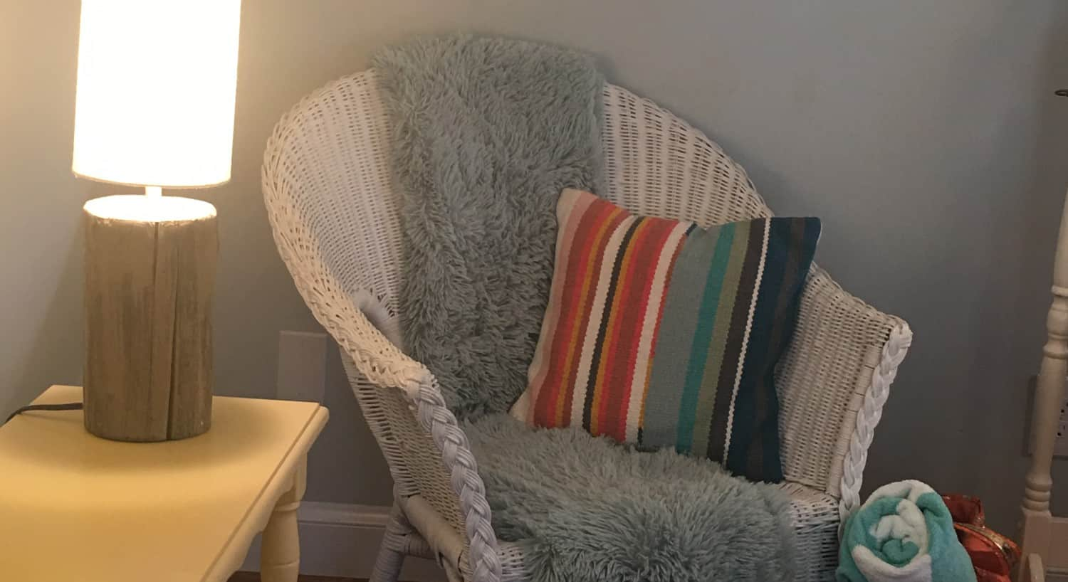 A white wicker arm chair with a cozy throw and pillow sits next to a table with a lamp.