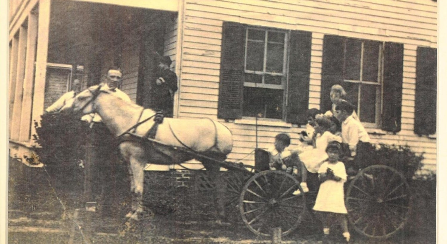 Vintage photo of a family in a horse-drawn buggy pulling up to a porch of a white house.