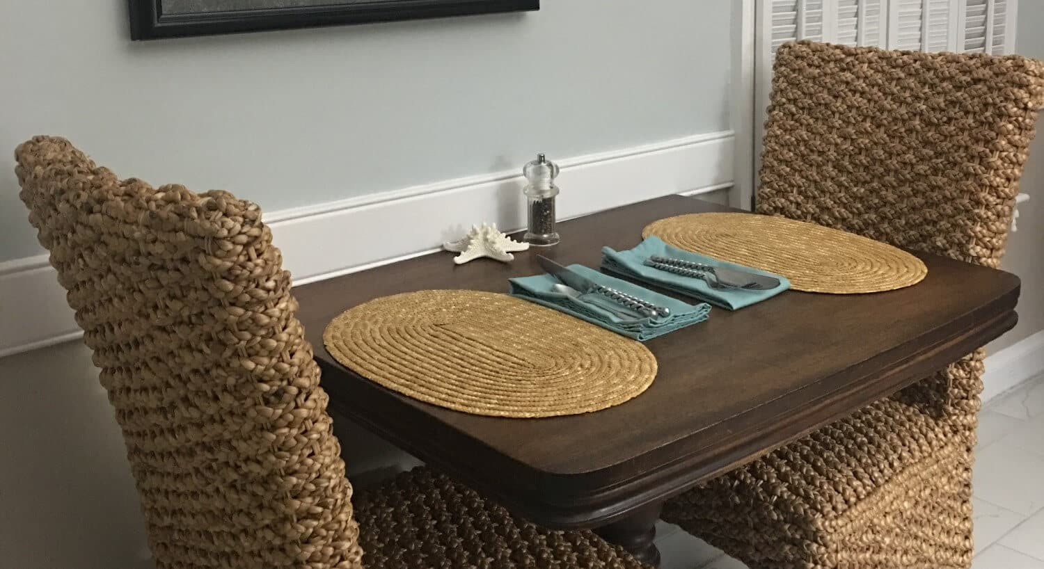 Table with wicker chairs  set for two  with placemats and cutlery.