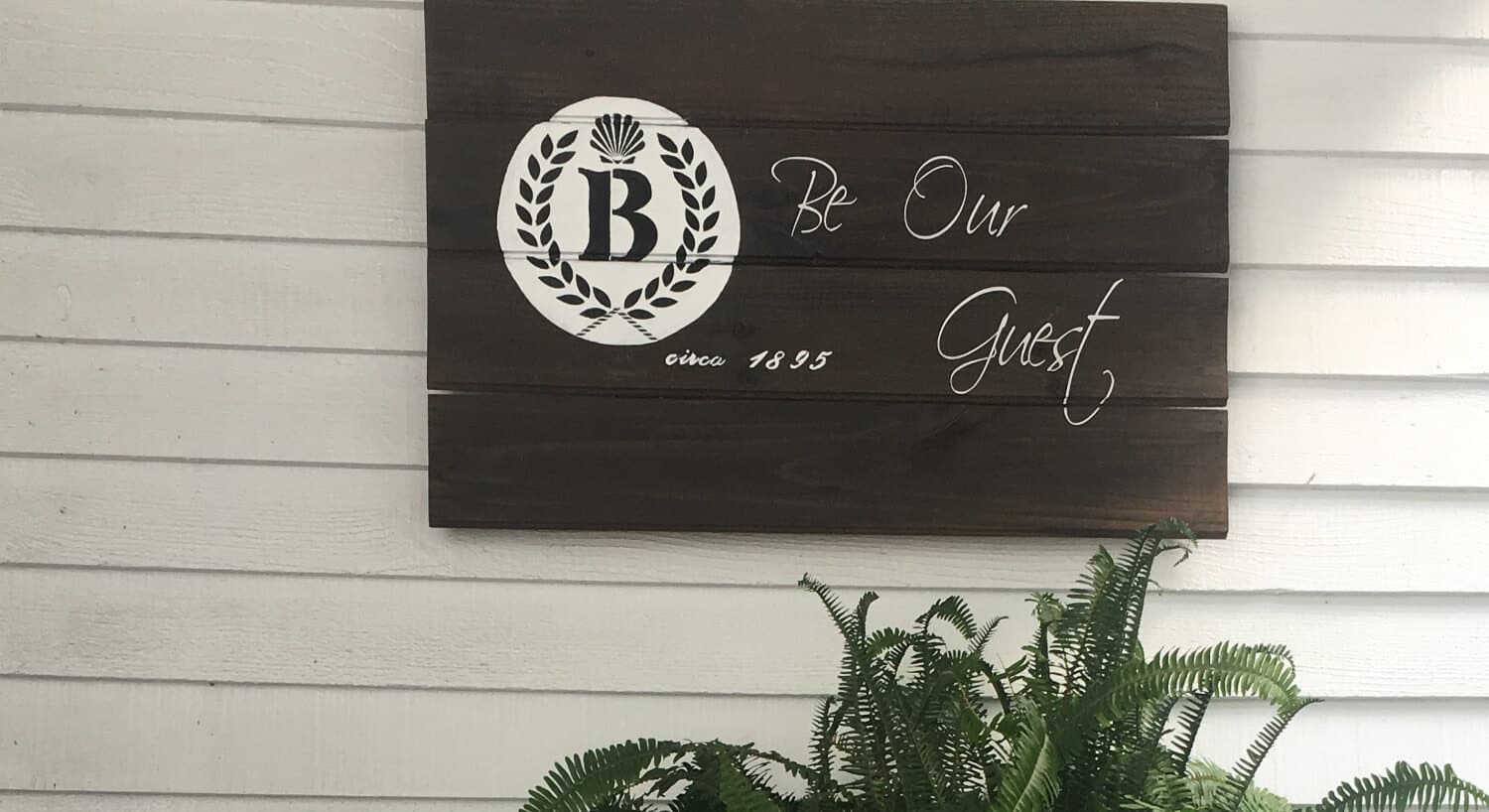 "Brown wooden sign hanging on an exterior wall that says, ""Be Our Guest"" with the Barclay Cottage Bed & Breakfast logo."