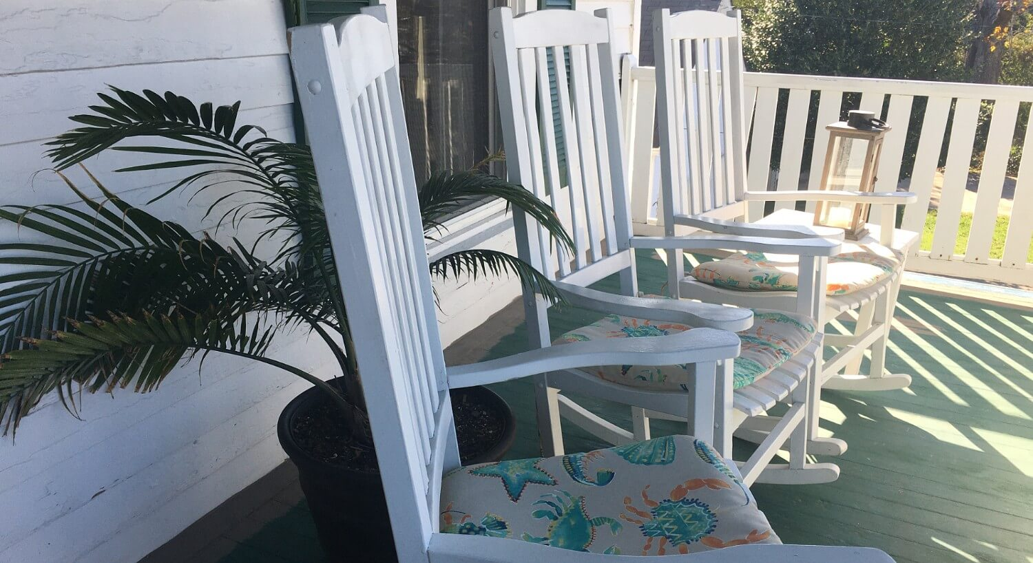 Row of white rocking chairs with pads on a sunshine-filled porch.