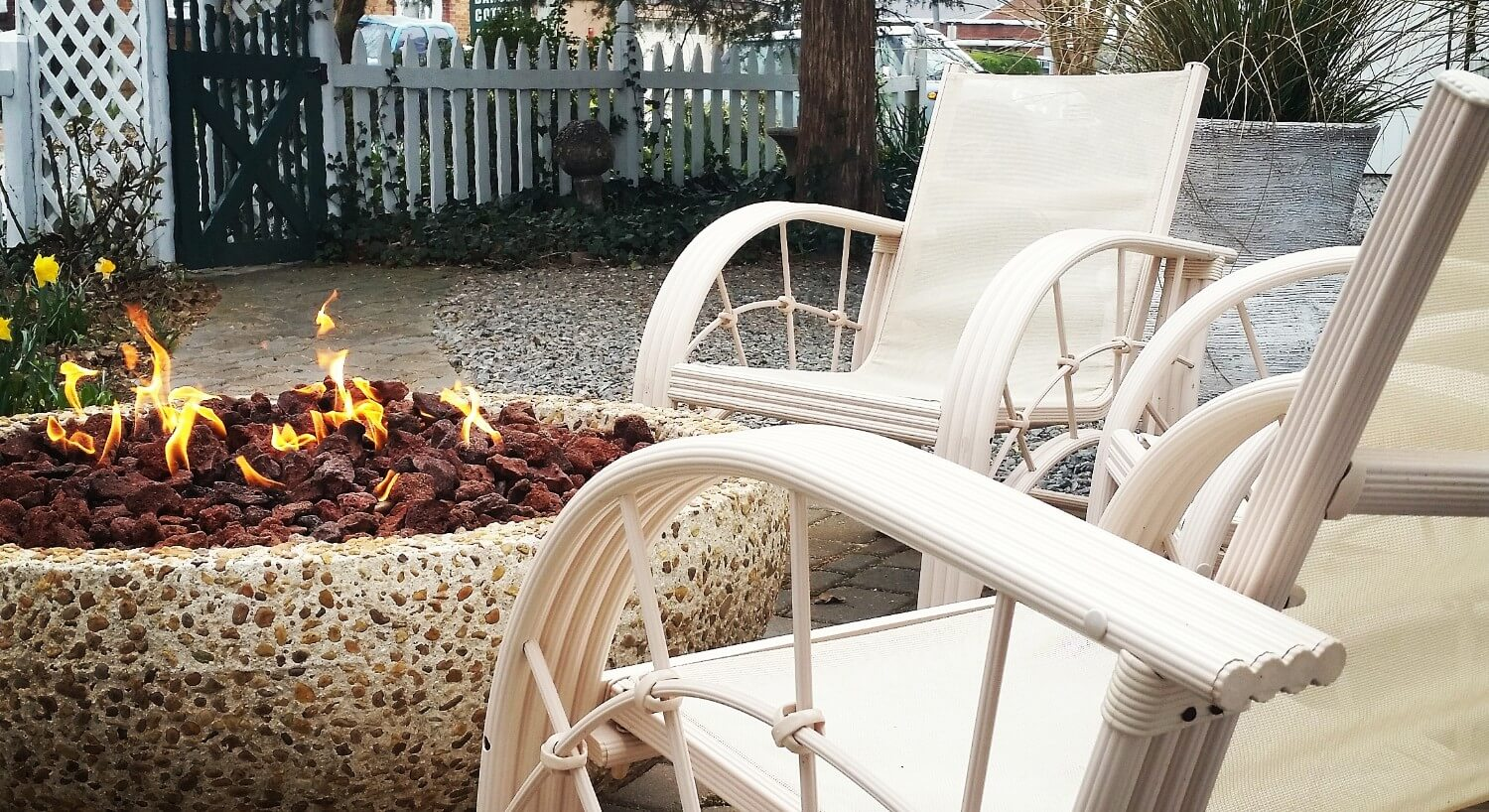 White chairs surround a unique fire pit in an outdoor patio next to a fence.