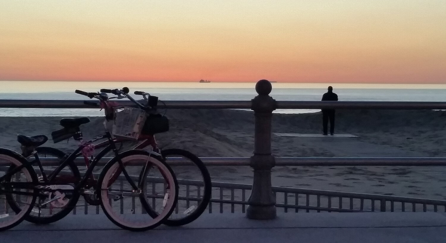 Two bikes on a boardwalk overlooking the beach at sunset.