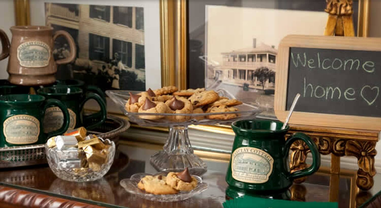 "Cookies and treats on a sideboard with hand-thrown clay mugs and a sign that says ""Welcome Home"""
