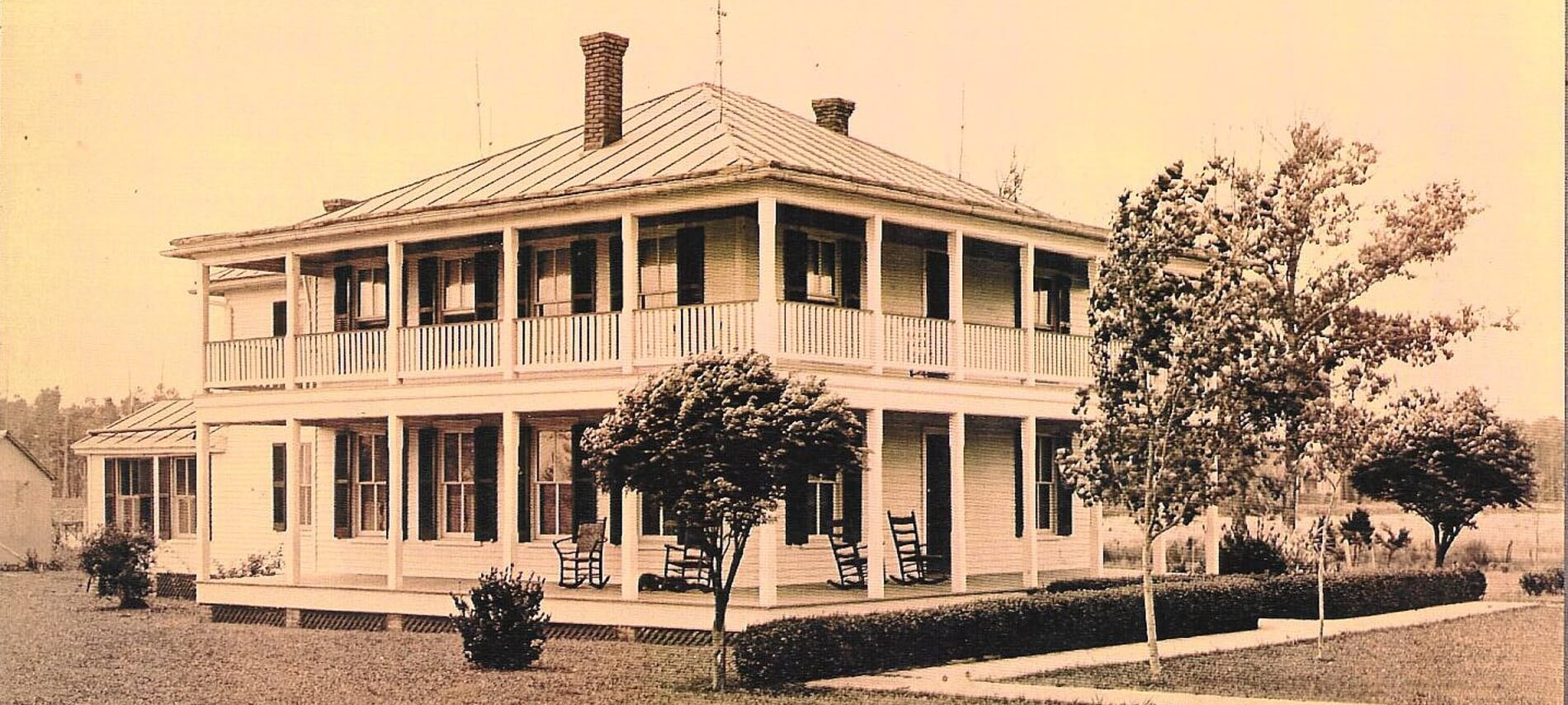 Sepia toned photo of Barclay Cottage Bed & Breakfast in past times- large white home with two-story wrapped porch.