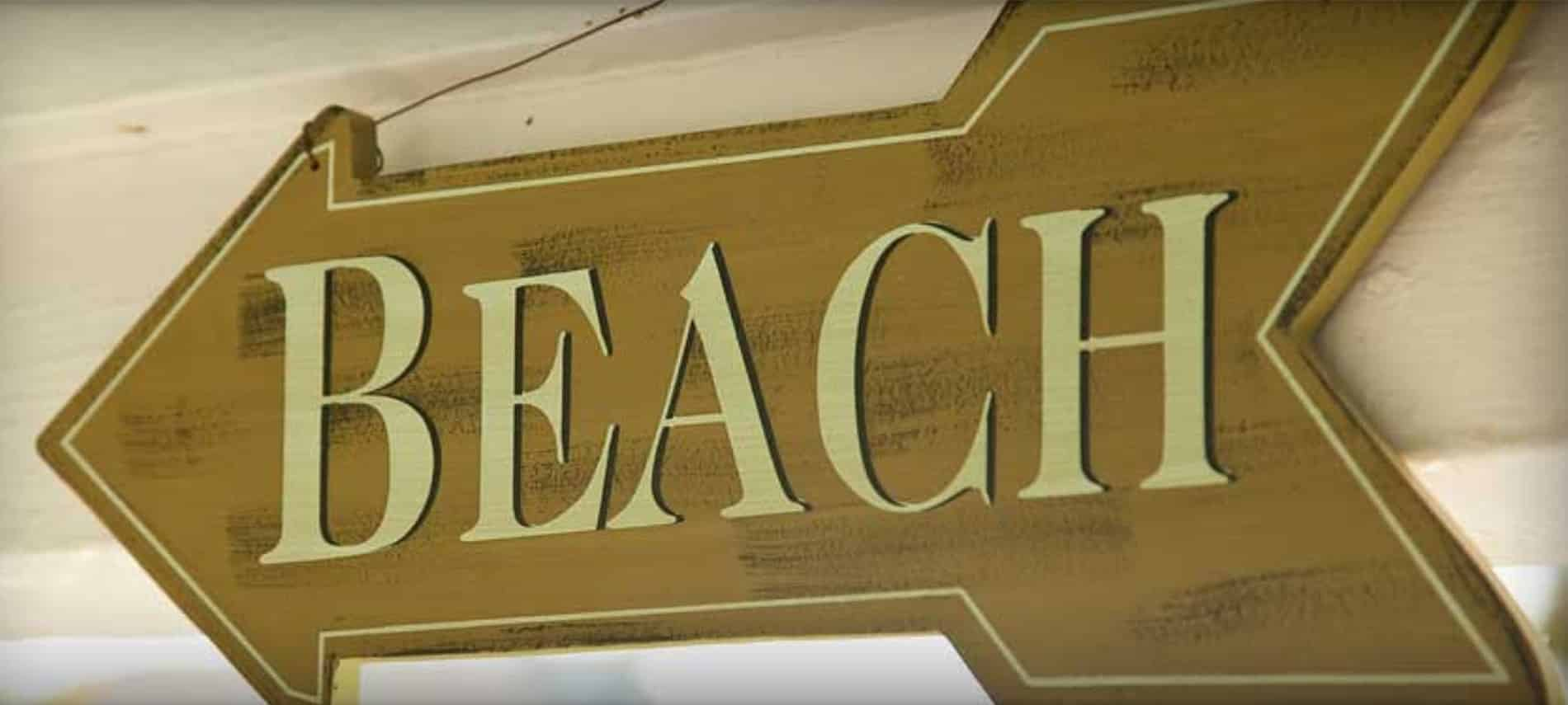 """Large wooden arrow sign with the word """"BEACH"""" in beige capital letters."""