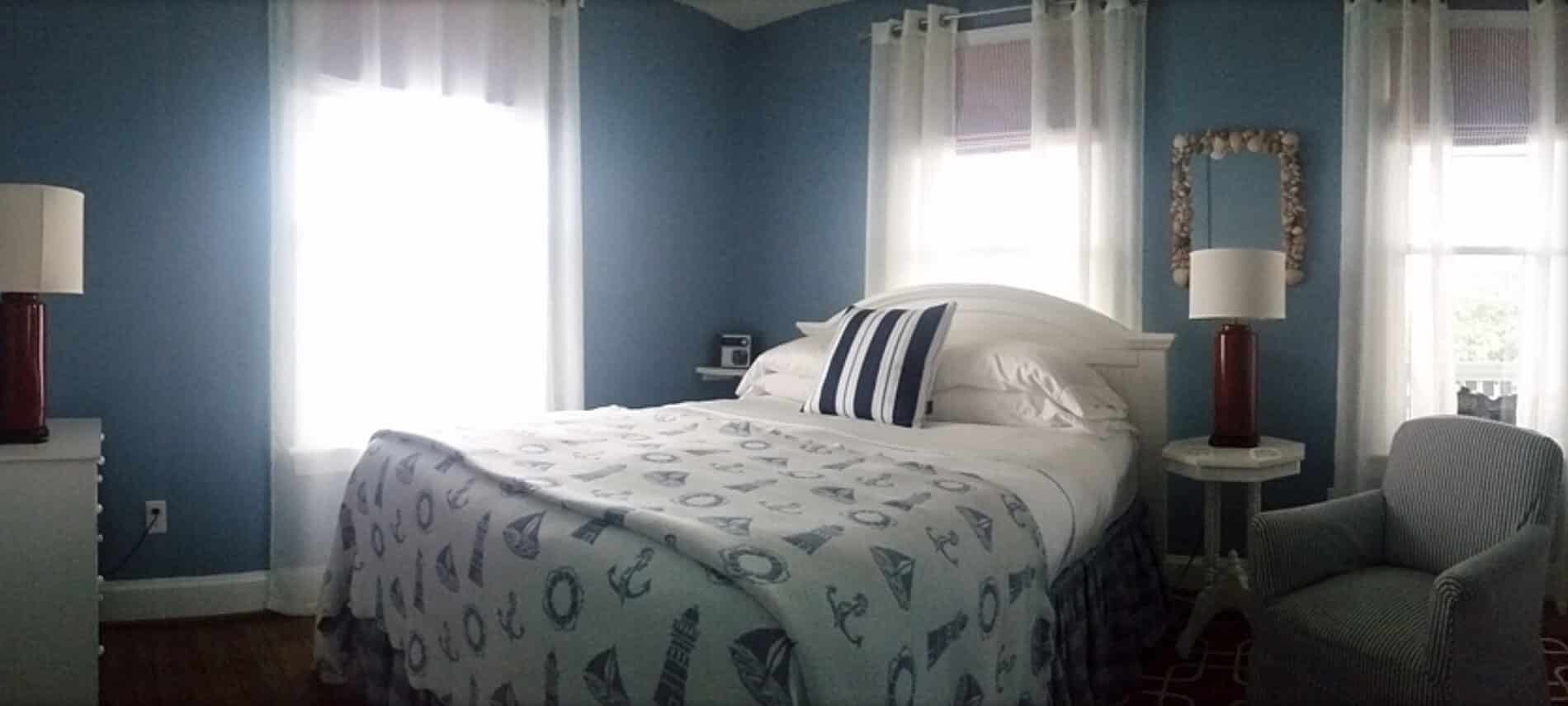 A bed made up in white and blue nautical bedding next to a nightstand with a light and an armchair.