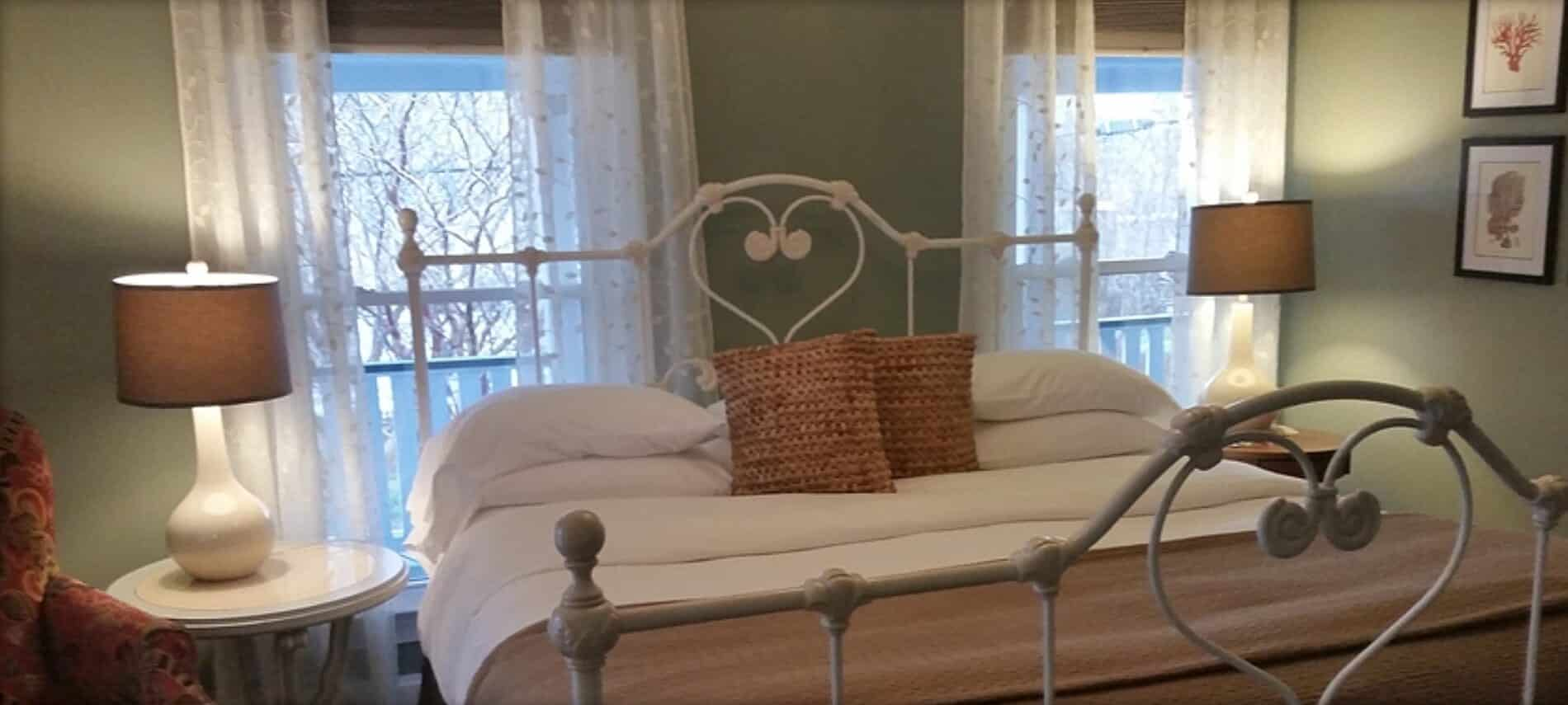 White iron bed with several pillows sits under two windows with sheer curtains.