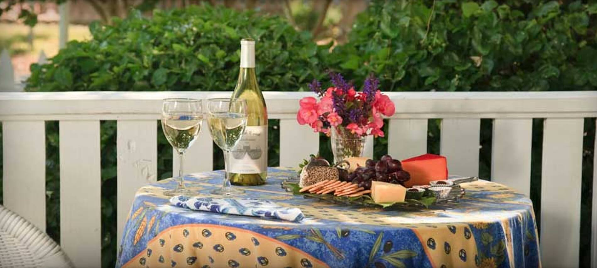 Bottle of white wine with glasses and a cheese tray on a covered table outdoors.