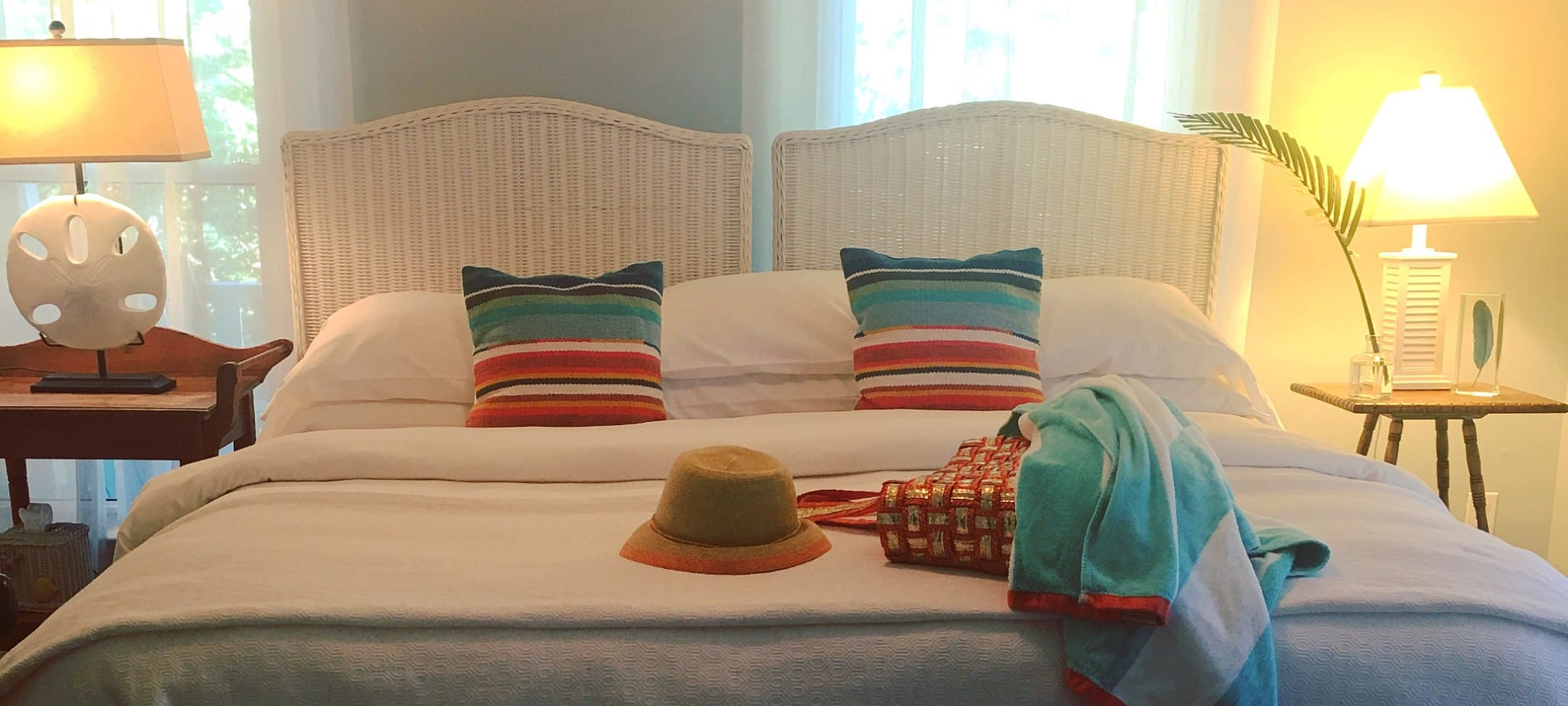 A large bed with two wicker headboards made up in white with colorful pillows and two nightstands with lamps.