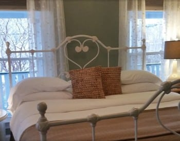 Iron bedframe with bed made up in white and tan between two large windows with sheer curtains.