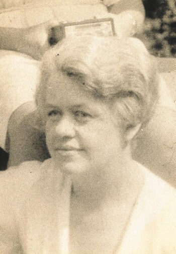 Vintage portrait of a woman with a soft up-done hairstyle and a white blouse.