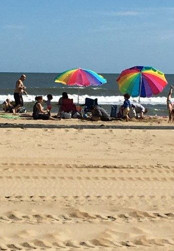 A group of people on the beach with rainbow beach umbrellas.