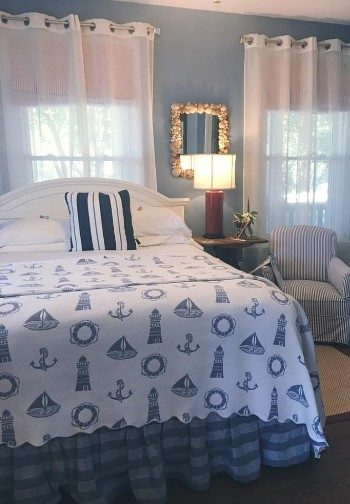 A bed made up in white and blue nautical bedding next to a nightstand with a light and a chair with striped cover.