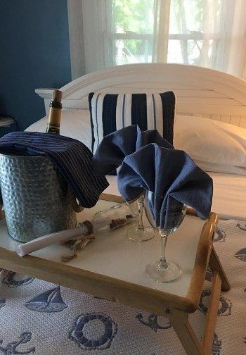 A tray with wine in a bucket and two wine glasses with blue napkins on a bed.