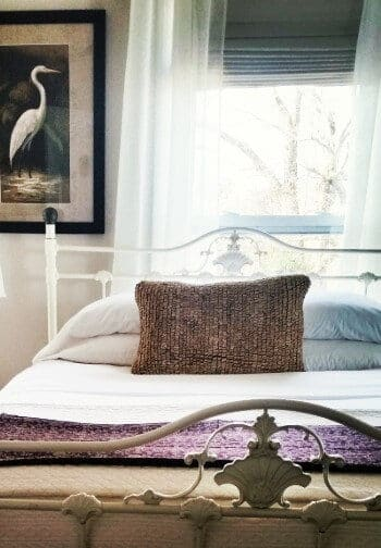 Iron bedframe with bed made up in white and tan under a large window with sheer curtains and a bird painting.