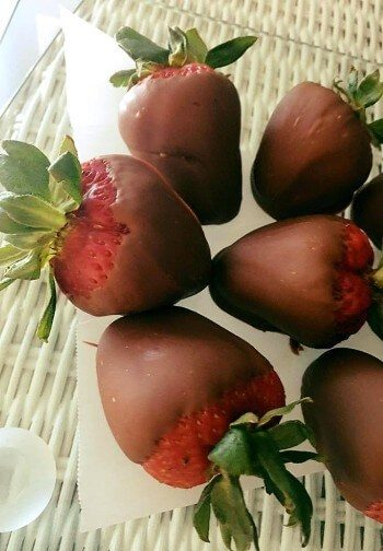 Six chocolate-covered strawberries rest on parchment over a white wicker table.