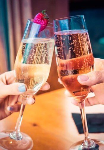 Two champagne flutes are toasted by women with pink and blue nail polish.