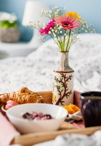 Breakfast tray with croissant and cereal alongside a cup of coffee and vase of colorful flowers.
