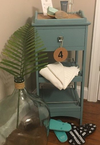 A side table painted teal next to a glass jug and two pairs of flip-flops with a #4 tag hanging from it.