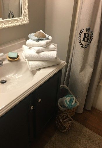 Stack of white towels and soap on the edge of a vanity sink next to a shower curtain with a B logo.
